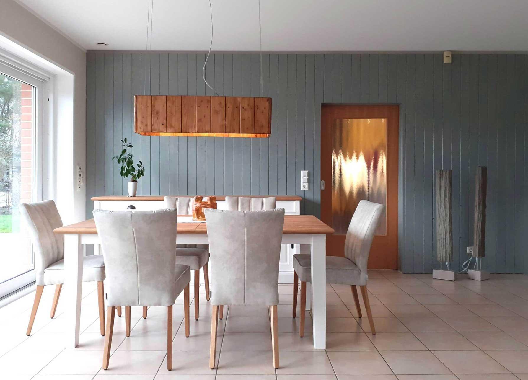 Die vertikale Holzschalung in Blau-Grau streckt den Raum optisch.